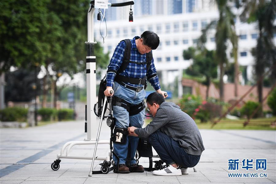 下肢助行外骨骼机器人可以穿戴在人体上,通过膝盖和髋关节位置的驱动系统带动人体腿部运动,实现行走。机械结构的设计基于人体工程学和仿生学机理,贴合人体,保证患者穿戴的舒适性。图为:12月11日,在中科院深圳先进技术研究院,智能仿生研究中心研究助理马勋举(右)在室外测试时帮助高级工程师彭安思穿戴下肢助行外骨骼机器人。
