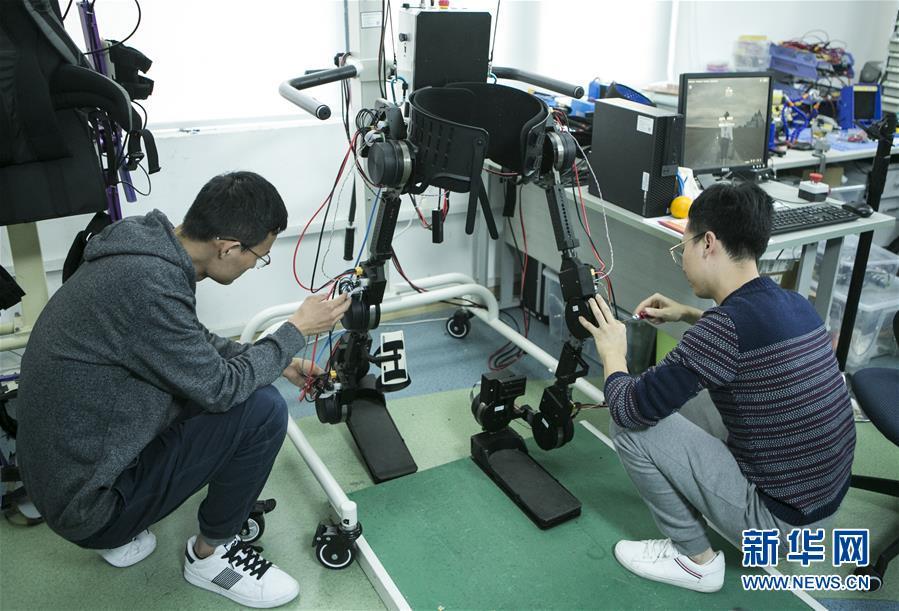 12月11日,在中科院深圳先进技术研究院智能仿生研究中心实验室,研究助理马勋举(左)和博士后李南在调试最新的自平衡下肢外骨骼机器人。
