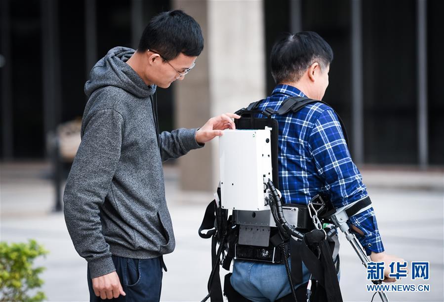 12月11日,在中科院深圳先进技术研究院,智能仿生研究中心研究助理马勋举(左)在室外测试时帮助高级工程师彭安思调整下肢助行外骨骼机器人。